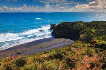 Plaża Muriwai - w oddali widać skałę na której znajduje się kolonia głuptaków. Na plaży praca stworzona przez lokalnego artystę.